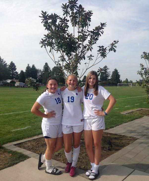 Freshmen Megan Lyver, Emily Miller, and Colby Jansen pose together  as they wait for team pictures