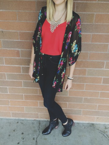 Junior Trinity Swift is wearing high-waisted jeans, booties, a bright flowy tank top, floral kimono, and a bold necklace. All of these pieces form a lively spring outfit.