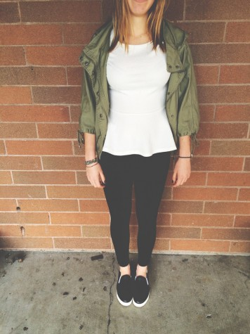 Junior Natalie Herder is wearing a peplum top, army green jacket, black pants, and slip on vans. This is a great outfit for a cool spring day.