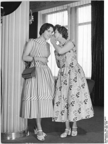 """Zentralbild-Salzbrenner We-Th 27.3.1956 Von der Idee bis zum fertigen Modell. Es ist eine unbestreitbare Tatsache, daß der Frühling den Winter mit seinen Schnee- und Eismassen nun endgültig verdrängt hat. Genau so unbestreitbar ist es jedoch, daß mit der zunehmenden Erwärmung die """"Kleidersorgen"""" unserer Frauen in den Vordergrund treten. Wer von ihnen möchte nicht, wenn der Wintermantel nun für einige Monate """"eingemottet"""" wird, ein neues duftiges Kleid, nach dem neusten Schnitt der Mode sein eigen zu nennen? Diese """"Sorgen"""" hätten auch die Modeschöpfer unserer volkseigenen Bekleidungsindustrie, allerdings schon reichlich früher als die """"Konsumenten"""". Zu einer Zeit, da Schneestürme über das Land brausten und jeder froh war, sich in den warmen Wintermantel hüllen zu können, besprachen die Kolleginnen des VEB Kleiderwerk Dresden die neuen Sommermodelle und gingen an die Arbeit. UBz: (links) ein geschmackvolles Sommerkleid aus gesteiftem Zellwollgewebe. Die Taille ist etwas verlängert-der Rock leicht angekraust. Zur Unterbrechung des Streifenmusters sind Schrägblenden an Kragen und Rock drapiert. (rechts) Sommerkleid mit abgespalteter Taillenlinie und angekraust eingesetztem Rock. Material: Prägedruck (Bauentwicklung)"""