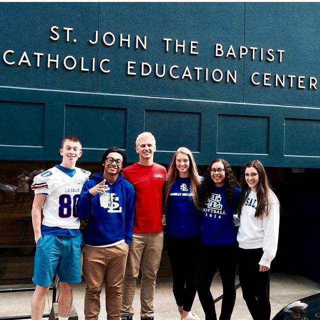 Patrick Dowhaniuk, Christian Reyes, Parker Cardwell, Emmerson Smith, Simone Stoney, and Emma Herder pose infront of one of the schools they visisted