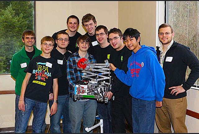 Last year's Robotics Club poses as they hold up one of their creations.