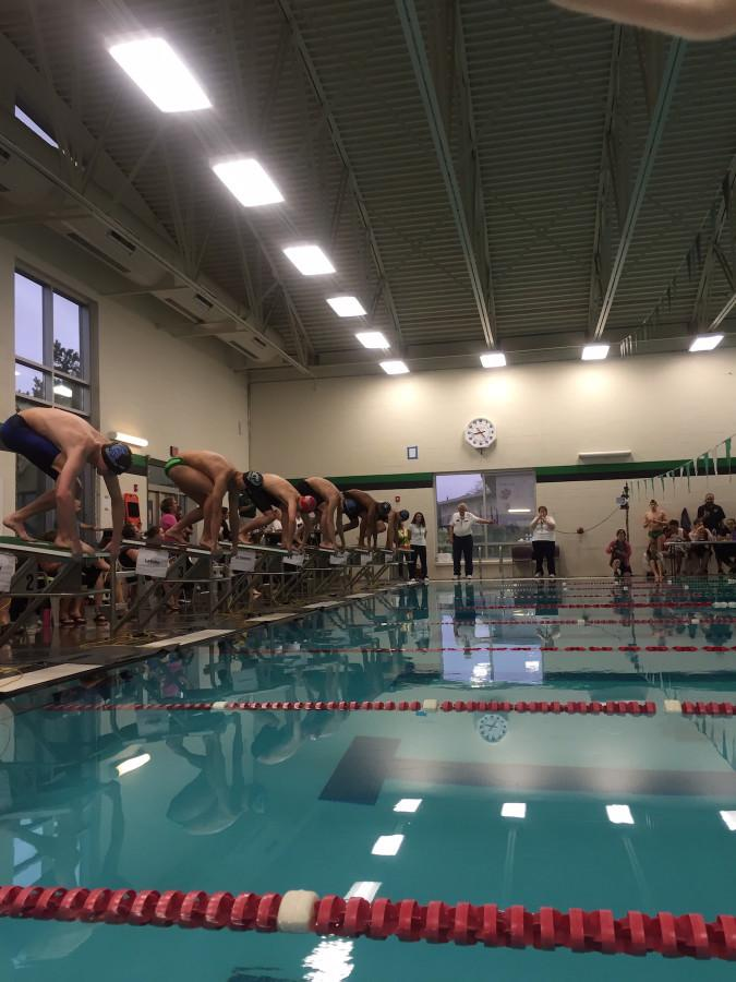 Keenan Robinson (center, with a red cap), qualified for the state meet in this 100 yard freestyle race, with a time of 49.05. That makes him the #3 seed heading into the state championships this weekend.