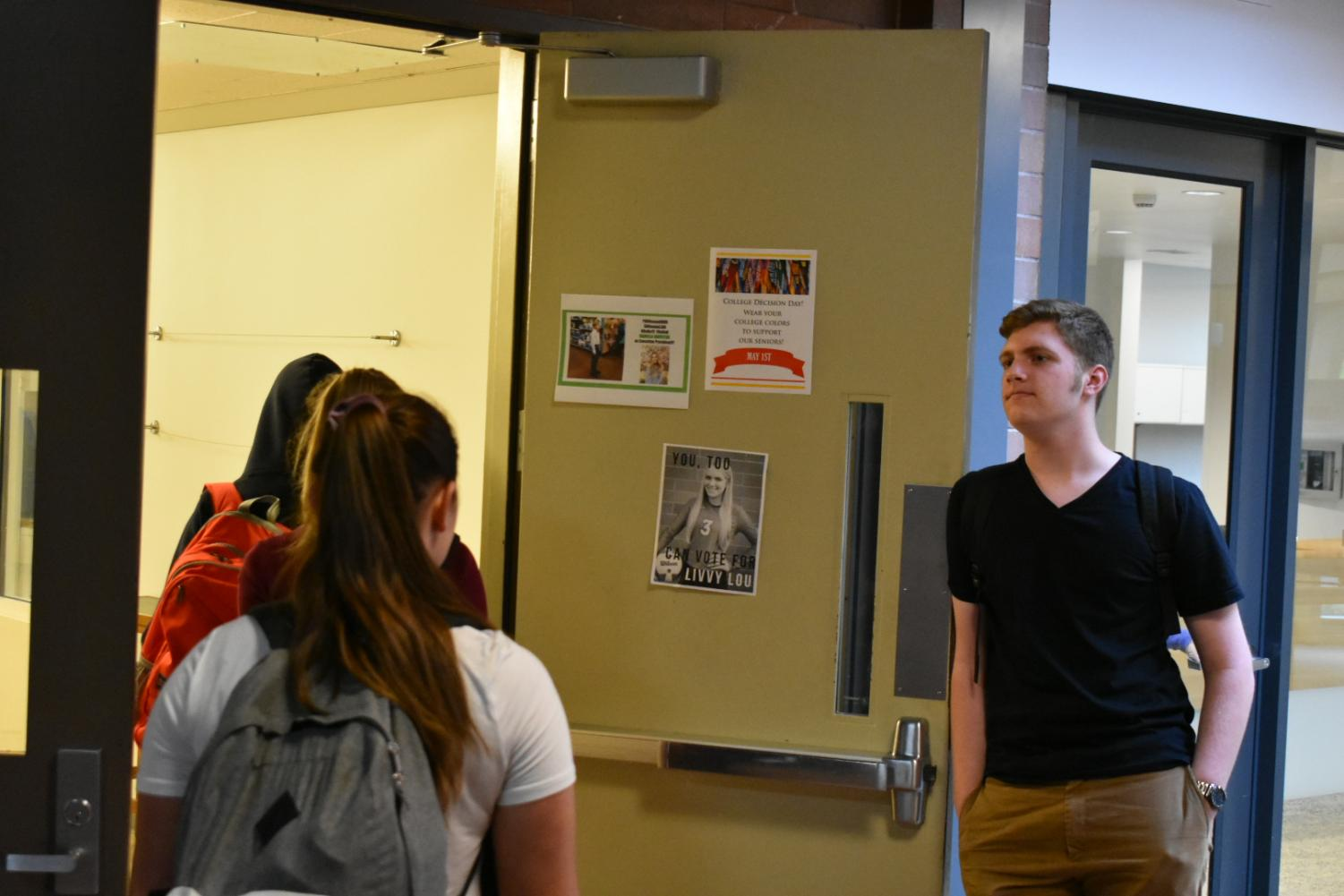 Luke Thompson holding the door for students walking to class after A lunch.