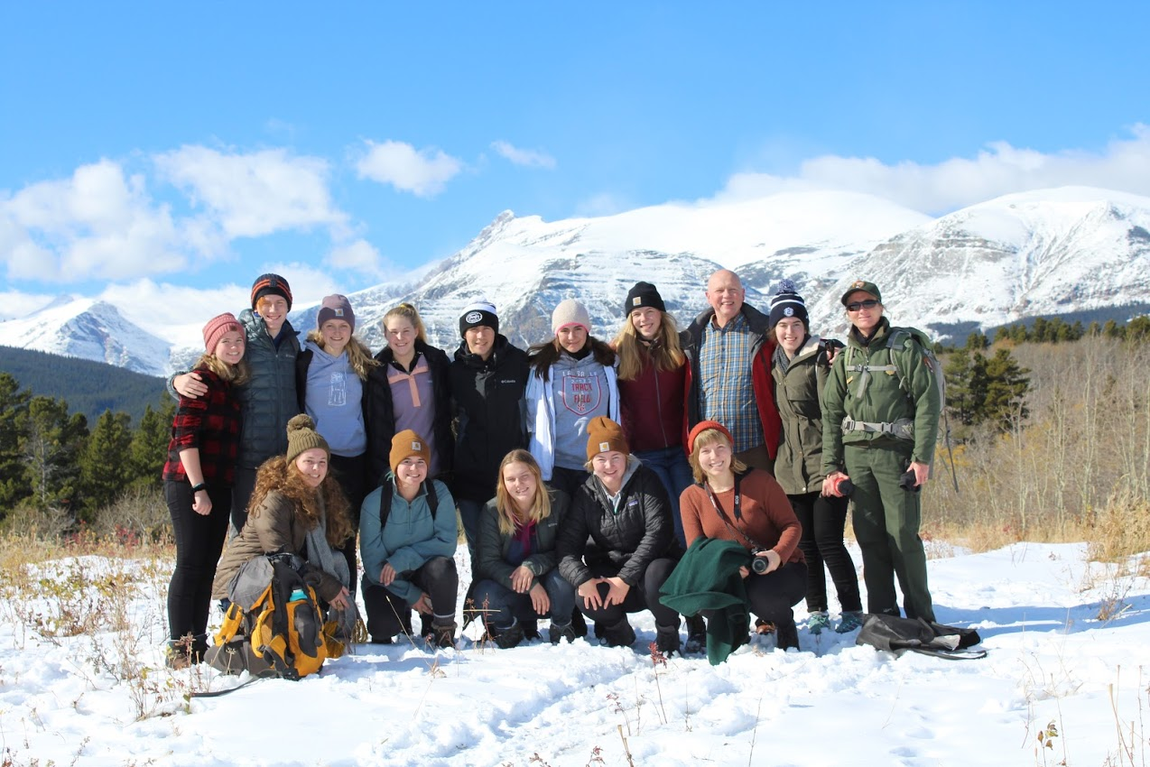 All 12 students, plus Ms. Dooley and Mr. Swanson, take a hike in East Glacier National Park, with beautiful mountains in the background.