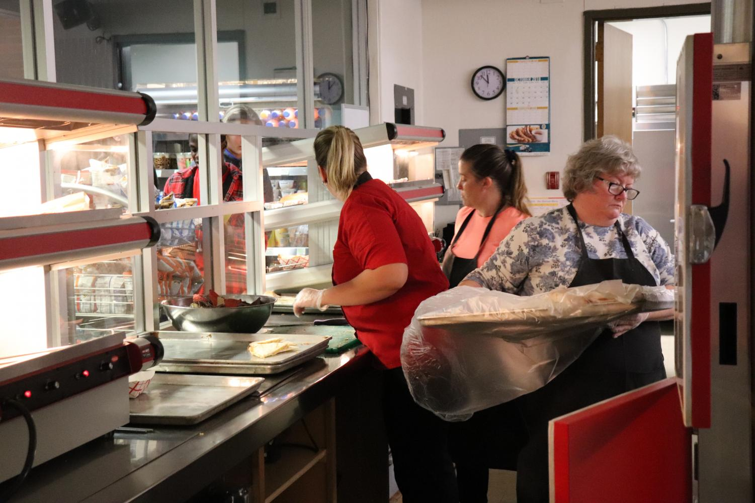 Ms. Gabel, Ms. McNassar, and volunteer Ms. Darnell Madrigal prepare and serve quesadillas to students.
