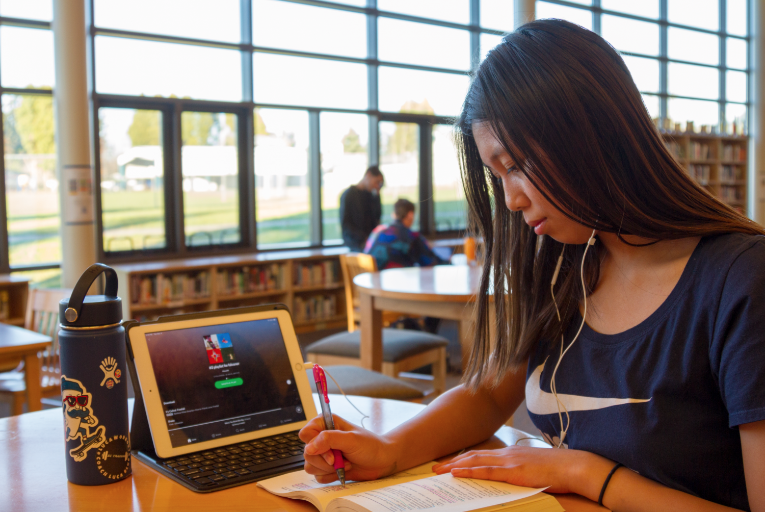 Junior Julia Tran listens to her Spotify playlist while working on homework in the library.