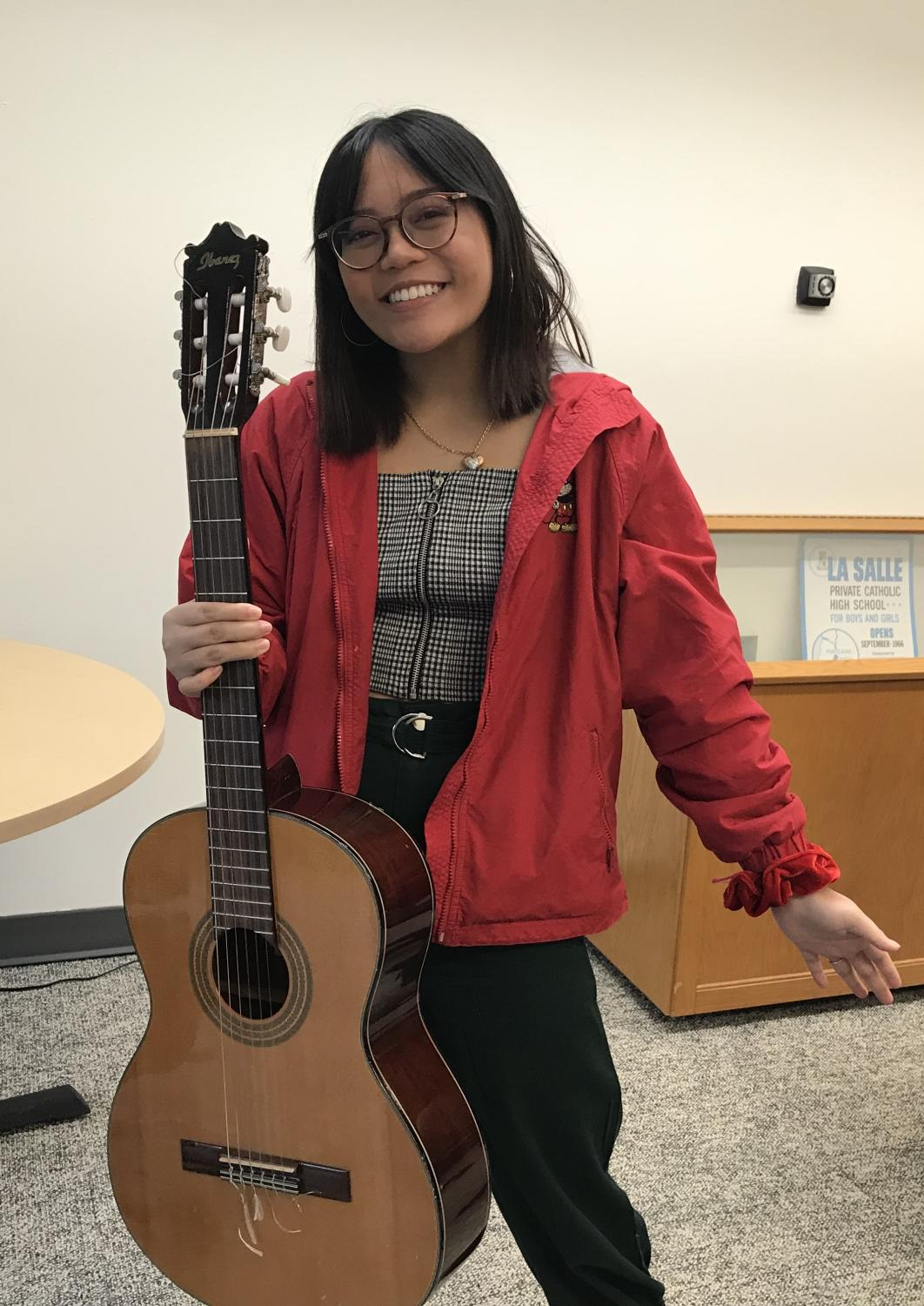 Junior Alison Paguio holding one of her favorite instruments to write songs with, her guitar.