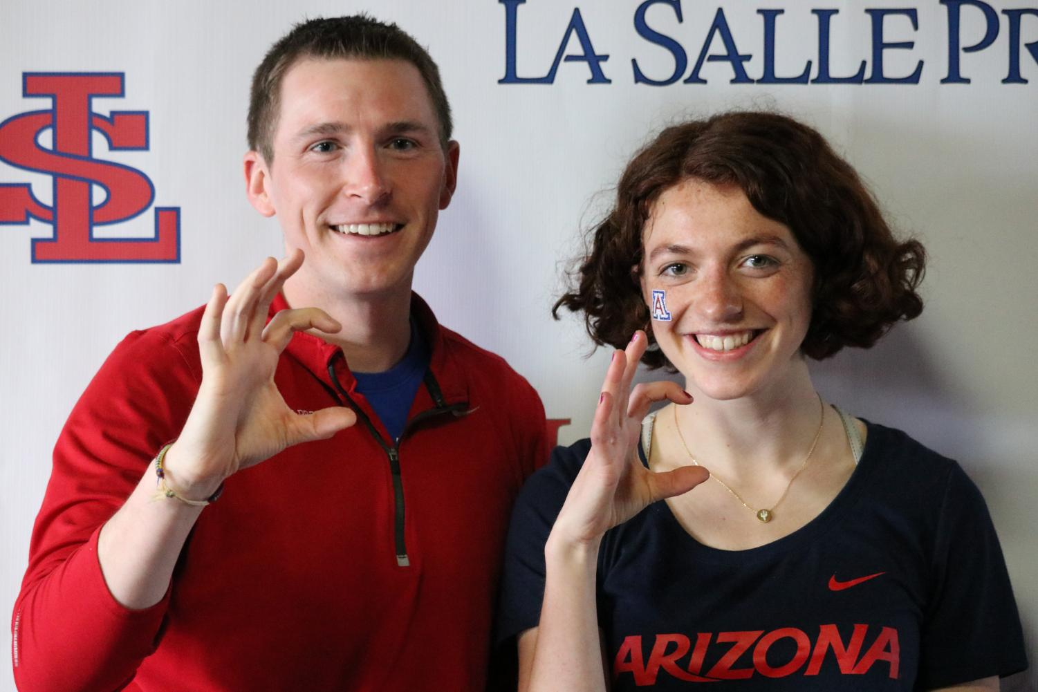 Hanley+and+head+track+coach+Mikel+Rathmann+pose+together+holding+up+the+Wildcats+symbol.