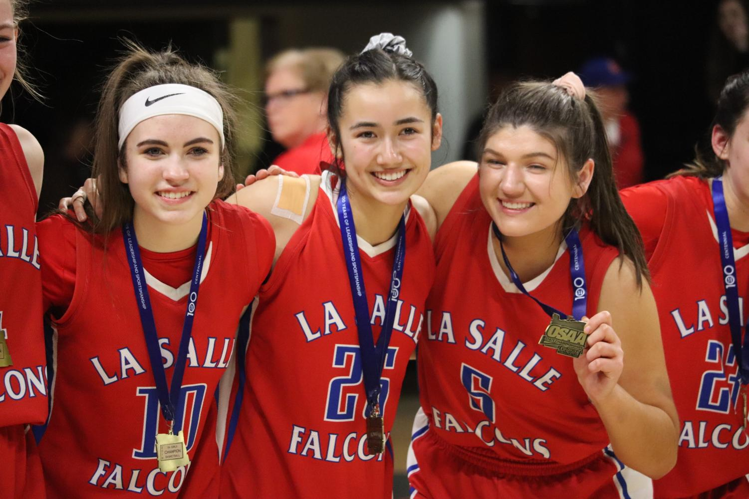 Sophomore+Mandy+Sisul+%28left%29+and+seniors+Miura+%28center%29+and+Jessie+Loboy+%28right%29+stand+side+by+side+to+show+off+their+new+medals.+
