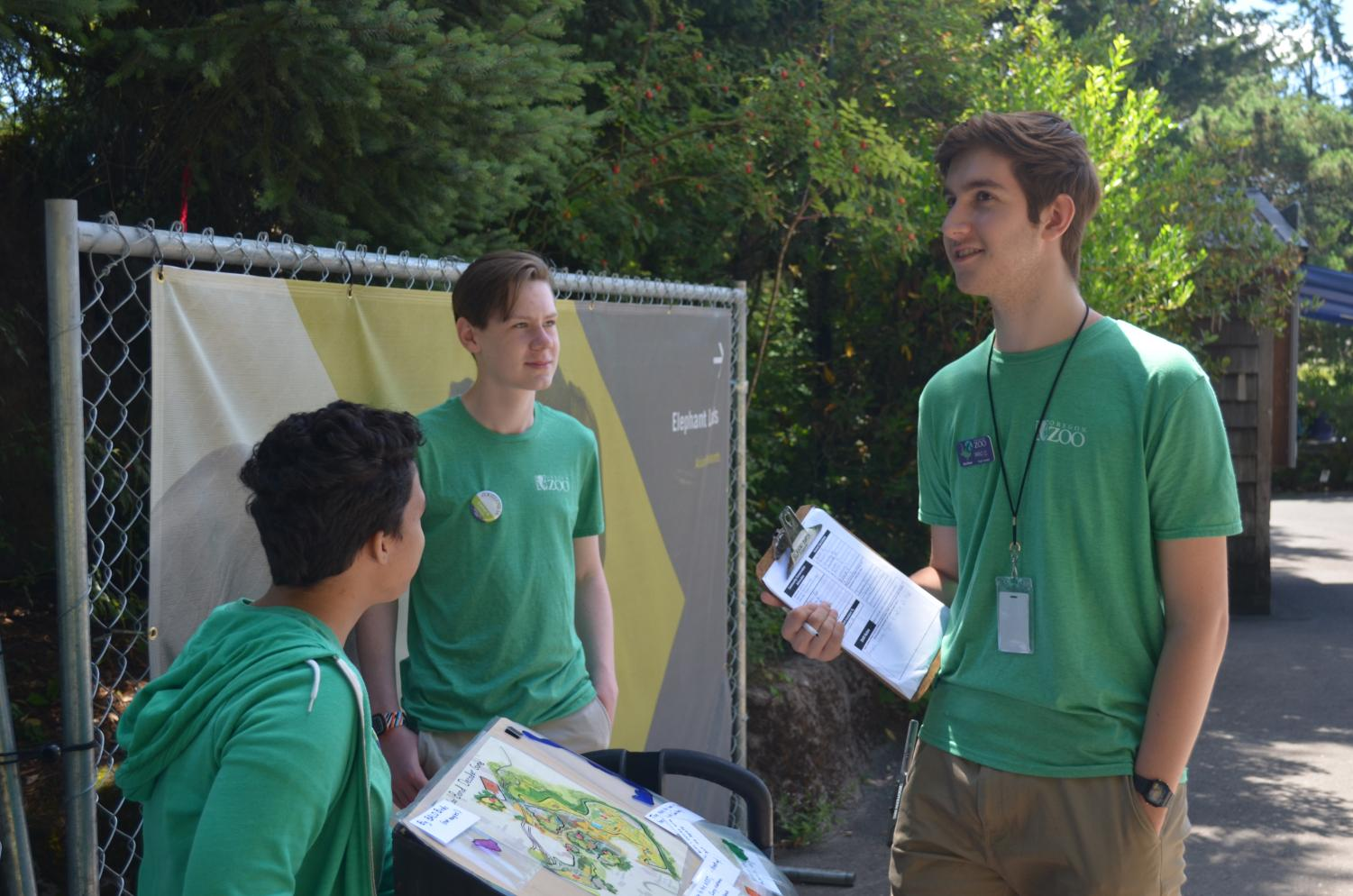 As a team leader, Callahan checks in with two ZooTeen interpreters who are running an activity about the Oregon Zoo bond measure.