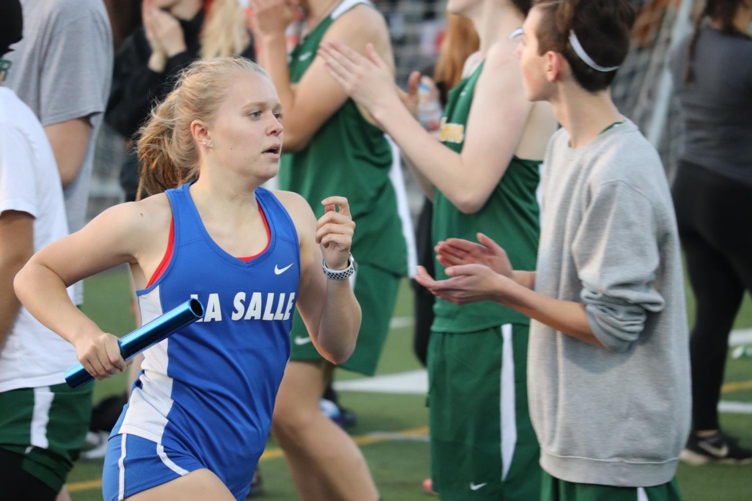 Junior Evelyn Bergler is cheered on by the rest of the team as she comes around the corner for the last straightaway of the 4x400 relay.