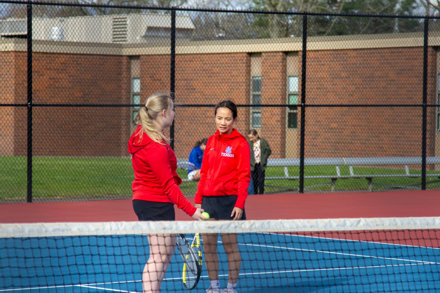 Senior+doubles+partners+Reilly+Nesen+and+Vu+discuss+their+strategy+before+the+next+play.