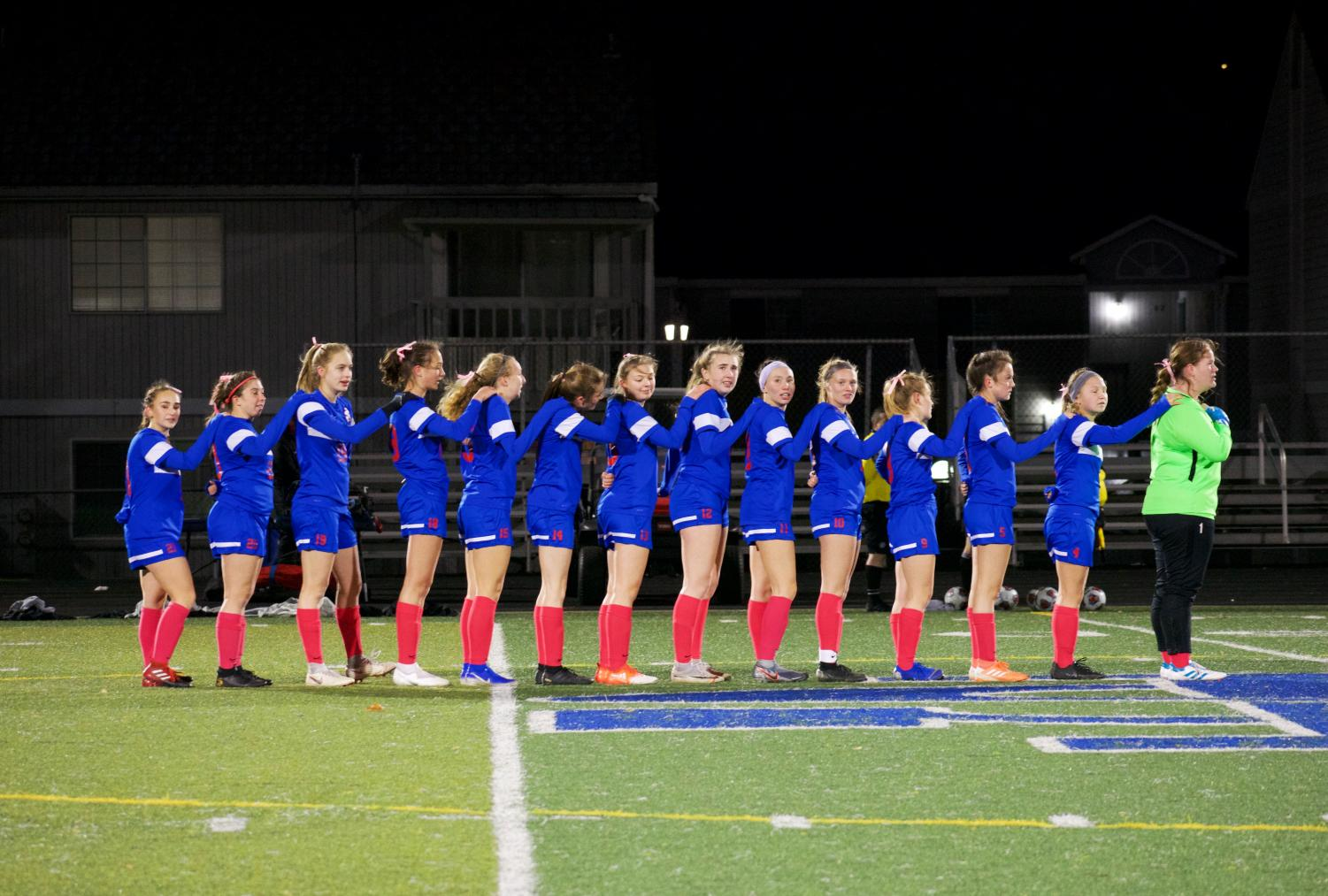 The+girls+soccer+team+stands+linked+together+during+the+national+anthem.