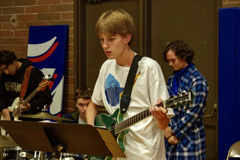 Senior+James+Kelly+plays+guitar+in+accompaniment+to+the+choir.