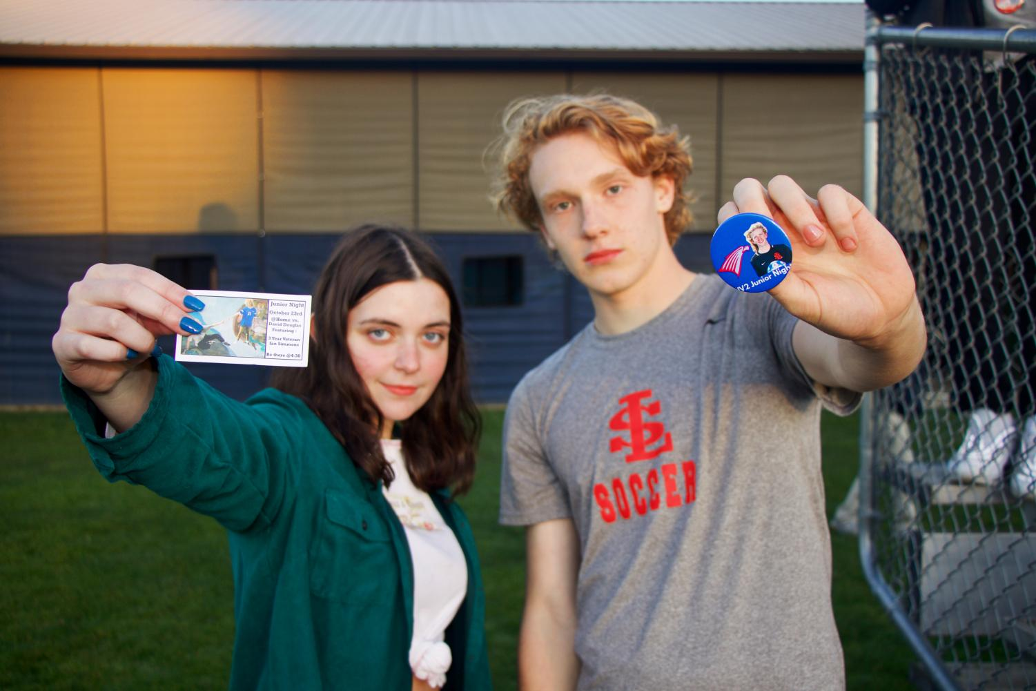 Juniors+Olivia+Pisaneschi+and+David+Jensen+pose+with+the+cutom+pins+and+cards+that+were+made+to+promote+junior+night.+