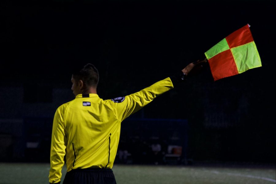 A referee shows what team is in possession of the ball.