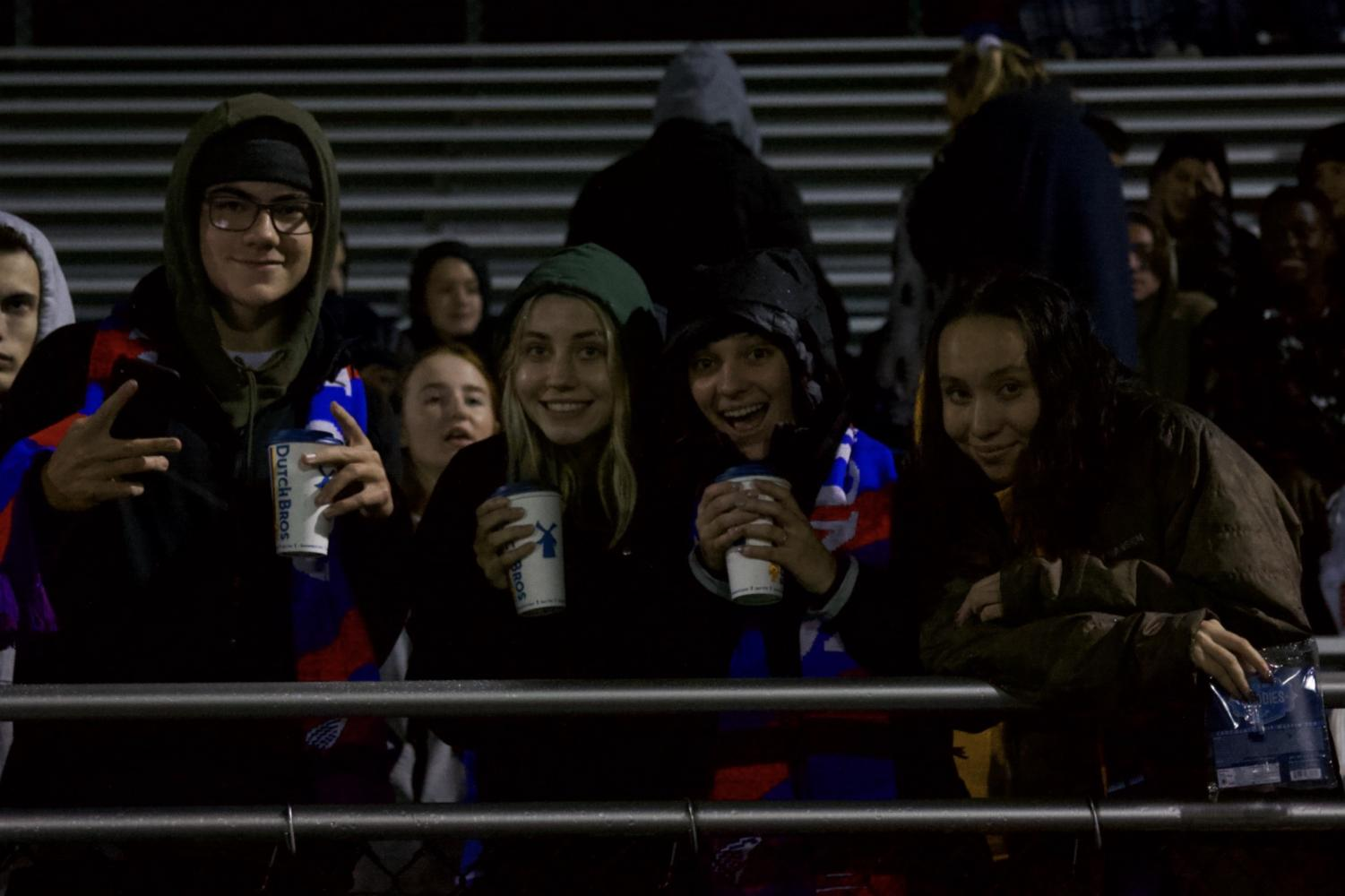 Students+cheering+on+the+soccer+team+in+the+rain.