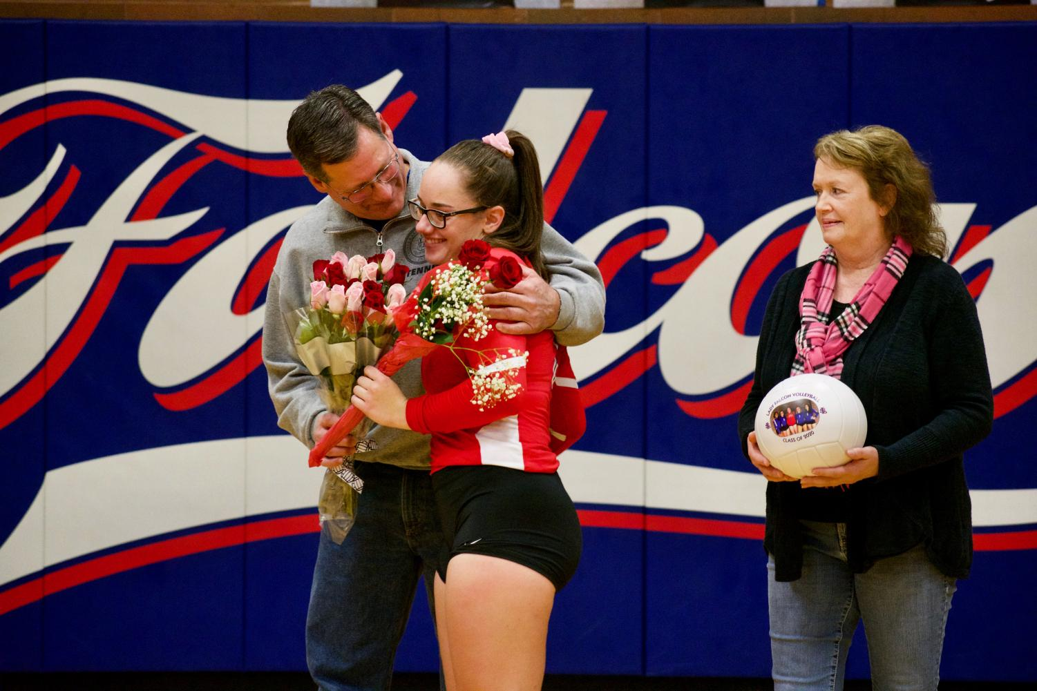 Ashley+Smith+is+recognized+at+senior+night+and+accompanied+by+her+parents.