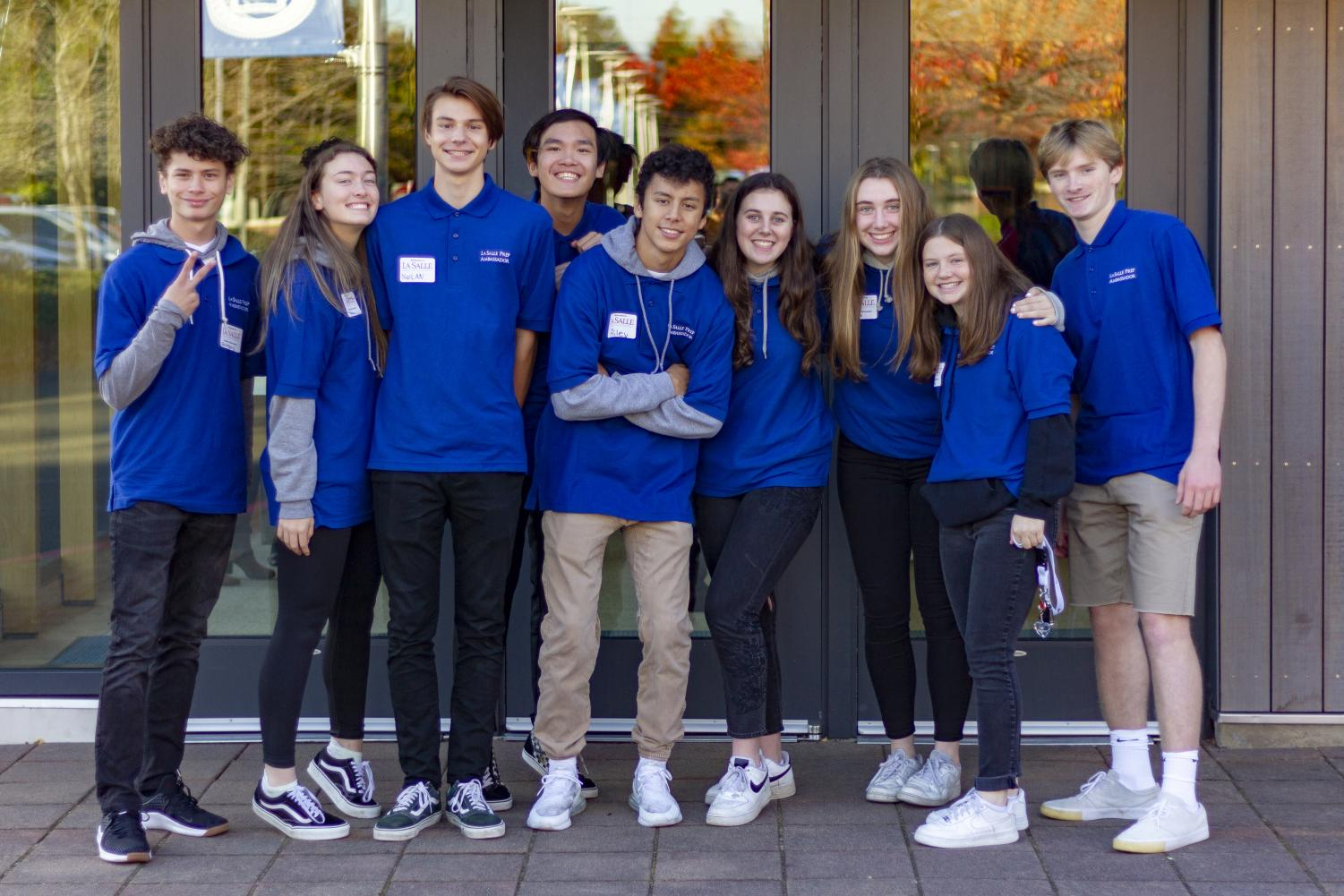 Student+ambassadors+pose+in+front+of+the+school+after+welcoming+visitors.