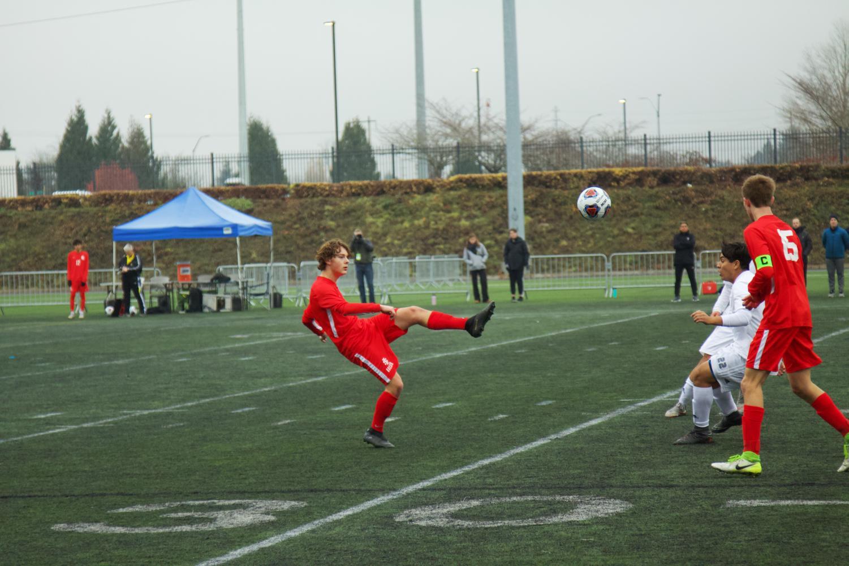 Senior+Ethan+Shea+kicks+the+soccer+ball+to+his+teammate.