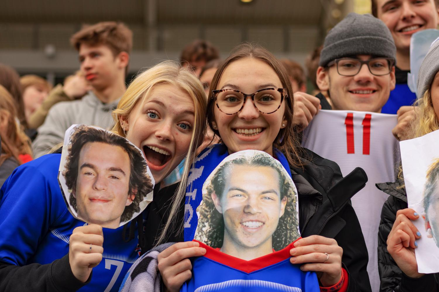 Junior+Lucy+Lawton+and+senior+Kari+Gutmann+cheering+players+with+cut-out+heads+of+seniors+Logan+Warner+and+Luke+Strange.