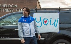 Counselor and former varsity boys soccer head coach Mr. Seth Altshuler stood near the front of the school and waved at students driving by.