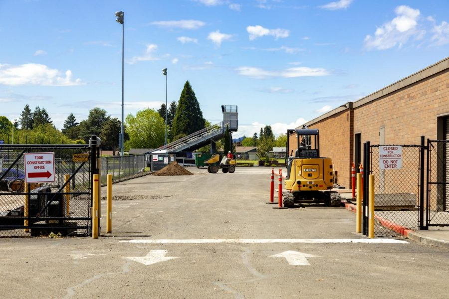 Construction vehicles in the side parking lot between the football field and future Saalfeld Athletic Center.
