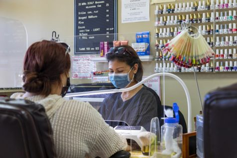 Nails Unlimited store manager Kim Nguyen works behind a clear plastic shield and wears a face mask.