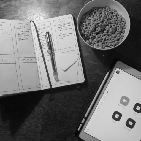 A paper planner with a bowl of Cheerios with an iPad with zoom open