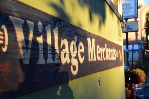 Village Merchants, located on Division Street, is characterized by its light green exterior.