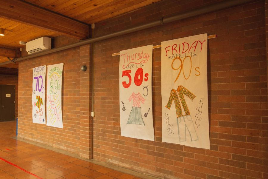 Made by the student council, posters in La Salle's halls display examples of how students could dress on each day of decades week.