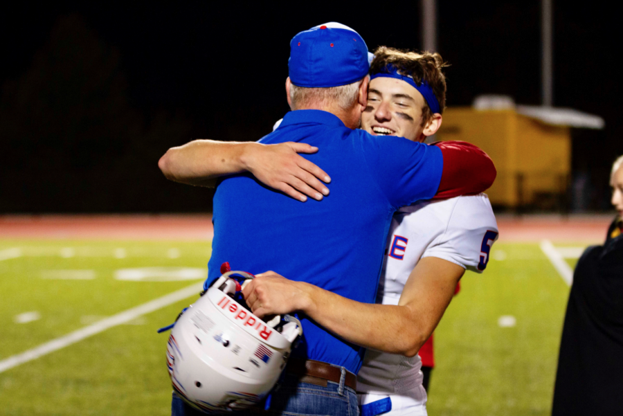 Rosumny embraces Mr. Tom McLaughlin, who is chaplain and waterboy for the football team, in a game from his junior year season.