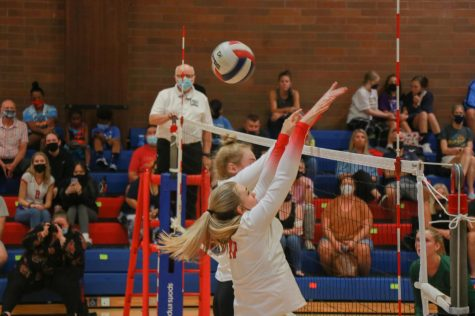 Lily Scherler and Olivia Maulding jump to block a spike.